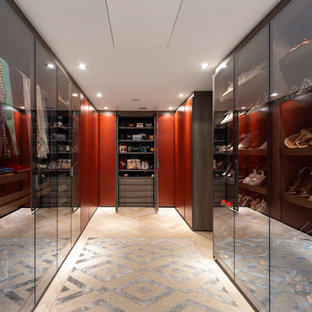 Contemporary gender neutral walk-in wardrobe in Surrey with glass-front cabinets and light hardwood flooring.