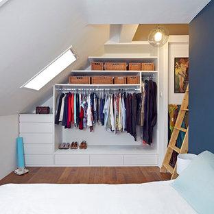 Exempel på en liten modern garderob, med mellanmörkt trägolv