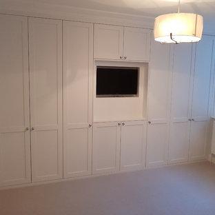 Esempio di un piccolo spazio per vestirsi per uomo minimal con ante in stile shaker, ante bianche, moquette e pavimento beige