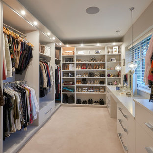 Inspiration for a medium sized contemporary dressing room in Other with carpet, flat-panel cabinets, white cabinets and beige floors.