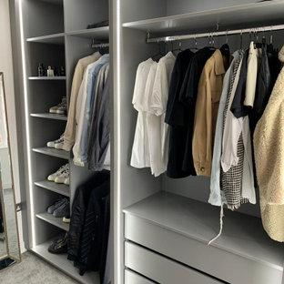 Immagine di uno spazio per vestirsi minimalista di medie dimensioni con nessun'anta, ante grigie, moquette e pavimento grigio
