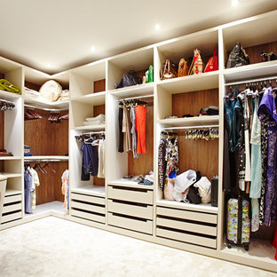 This is an example of a large contemporary gender neutral walk-in wardrobe in London with open cabinets, white cabinets and carpet.