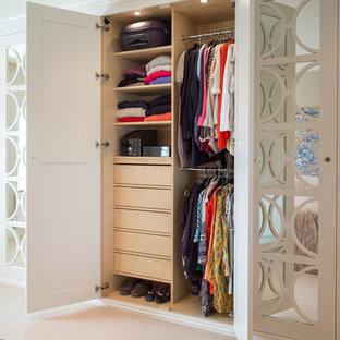 Klassisk inredning av en garderob för könsneutrala, med luckor med glaspanel, vita skåp, heltäckningsmatta och beiget golv