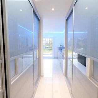 Imagen de vestidor unisex, moderno, de tamaño medio, con armarios tipo vitrina, puertas de armario beige, suelo de baldosas de porcelana y suelo blanco