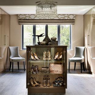Immagine di uno spazio per vestirsi per donna minimal con ante lisce, ante beige e pavimento in legno massello medio