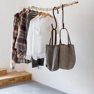 Bild på en mellanstor nordisk garderob, med betonggolv