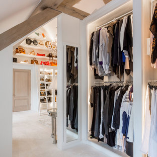Inspiration for an expansive country gender-neutral dressing room in West Midlands with open cabinets, white cabinets, carpet and white floor.