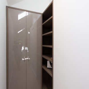 Photo of a large modern wardrobe in London with carpet and beige floors.