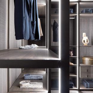 Foto di una grande cabina armadio unisex minimal con nessun'anta, ante in legno bruno e pavimento in cemento