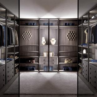 ドーセットの広い男女兼用コンテンポラリースタイルのおしゃれなフィッティングルーム (オープンシェルフ、濃色木目調キャビネット、コンクリートの床) の写真