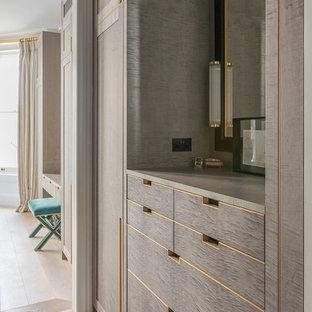 Diseño de vestidor de hombre, tradicional, grande, con armarios con paneles lisos, puertas de armario de madera oscura, suelo de madera clara y suelo beige