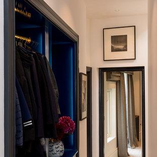 Imagen de vestidor unisex, bohemio, pequeño, con armarios abiertos, puertas de armario azules, suelo de madera en tonos medios y suelo marrón