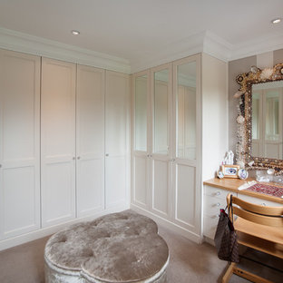 Inspiration for a medium sized contemporary gender neutral dressing room in Hertfordshire with shaker cabinets, white cabinets, carpet and beige floors.