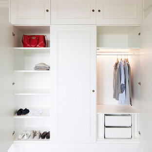 Inspiration for a classic gender neutral wardrobe in London with white cabinets, medium hardwood flooring and recessed-panel cabinets.
