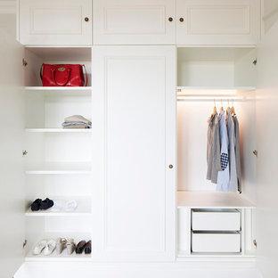 Ejemplo de armario y vestidor unisex, tradicional, con puertas de armario blancas, suelo de madera en tonos medios y armarios con paneles empotrados