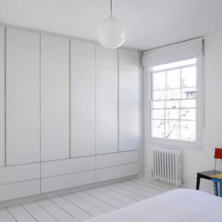 Exempel på ett stort modernt klädskåp för könsneutrala, med släta luckor, vita skåp, målat trägolv och vitt golv