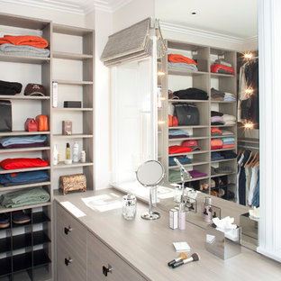 Example of a trendy walk-in closet design in London with gray cabinets