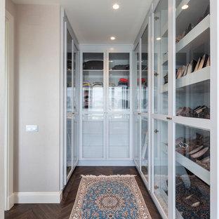 Ejemplo de armario vestidor unisex, clásico renovado, de tamaño medio, con armarios tipo vitrina, puertas de armario blancas y suelo de madera oscura