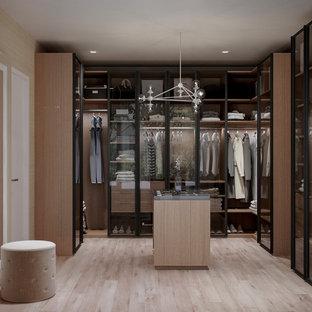Ispirazione per un grande spazio per vestirsi unisex contemporaneo con ante di vetro, ante in legno scuro e pavimento beige