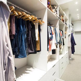 Immagine di una piccola cabina armadio unisex contemporanea con ante bianche, pavimento grigio, moquette e nessun'anta