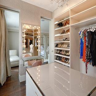 На фото: парадная гардеробная в современном стиле с белыми фасадами и темным паркетным полом с