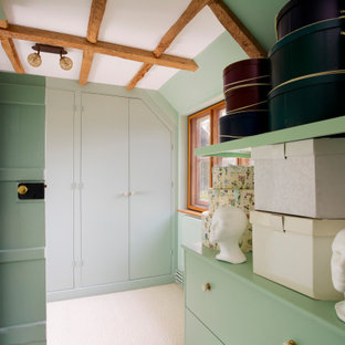 Photo of a rural walk-in wardrobe for women in Kent with flat-panel cabinets, green cabinets, carpet, beige floors and exposed beams.