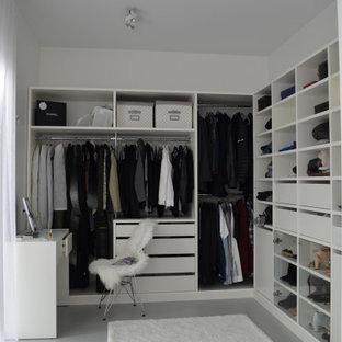 Foto di una piccola cabina armadio unisex minimalista con ante bianche, pavimento in cemento e pavimento grigio