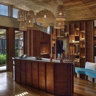 Foto di uno spazio per vestirsi tropicale con nessun'anta, ante in legno scuro, pavimento in legno massello medio e soffitto in legno