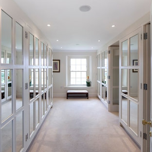 Walk-in closet - transitional gender-neutral carpeted walk-in closet idea in Gloucestershire with glass-front cabinets and white cabinets