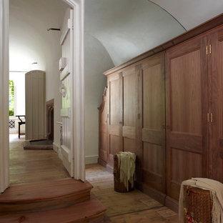 Modelo de vestidor unisex, tradicional, de tamaño medio, con armarios con paneles empotrados, puertas de armario de madera oscura y suelo de madera en tonos medios