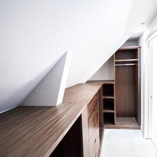 Klassisk inredning av ett mellanstort walk-in-closet för könsneutrala, med släta luckor, skåp i mörkt trä, betonggolv och grått golv