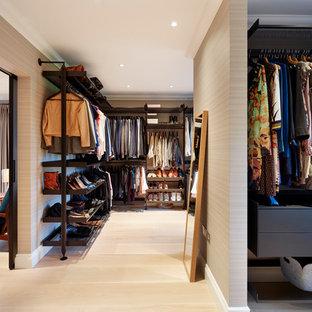 Diseño de armario vestidor unisex, contemporáneo, grande, con armarios abiertos, puertas de armario negras y suelo de madera clara