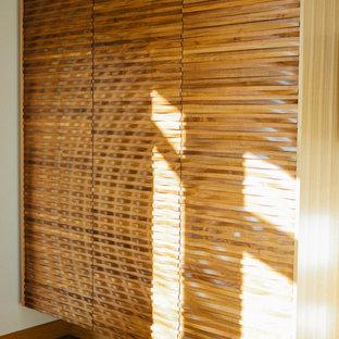 Imagen de armario unisex, actual, con puertas de armario de madera oscura y suelo de madera en tonos medios