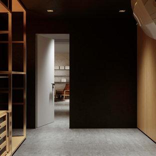 Esempio di un armadio o armadio a muro unisex nordico di medie dimensioni con ante lisce, ante in legno chiaro e pavimento in cemento
