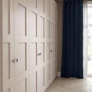 Imagen de armario clásico, de tamaño medio, con armarios estilo shaker, puertas de armario grises, suelo de madera en tonos medios y suelo marrón