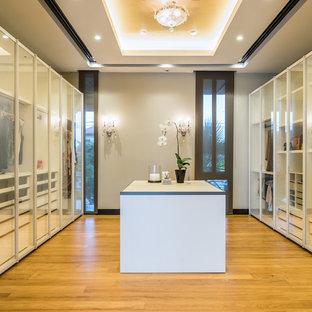 Idee per uno spazio per vestirsi contemporaneo con ante di vetro e pavimento in legno massello medio