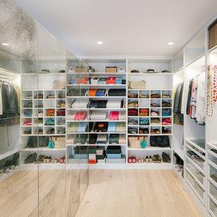 Modelo de armario vestidor de mujer, actual, de tamaño medio, con armarios abiertos, puertas de armario blancas, suelo de madera clara y suelo beige