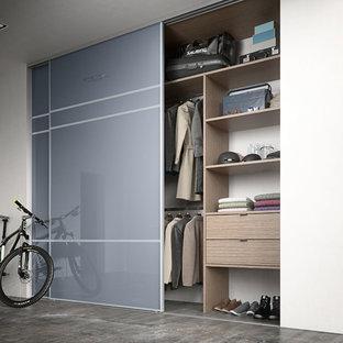 Foto di un grande armadio o armadio a muro unisex design con ante di vetro, ante in legno chiaro e pavimento in cemento