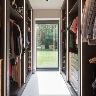 Photo of a contemporary gender neutral walk-in wardrobe in Surrey with flat-panel cabinets, dark wood cabinets, carpet and white floors.
