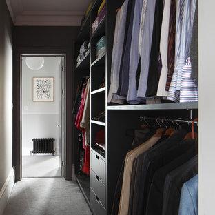 ロンドンの広い男女兼用トラディショナルスタイルのおしゃれなウォークインクローゼット (オープンシェルフ、グレーのキャビネット、カーペット敷き、グレーの床、格子天井) の写真