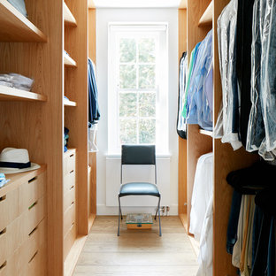 This is an example of a medium sized contemporary gender neutral walk-in wardrobe in London with open cabinets, light wood cabinets and light hardwood flooring.