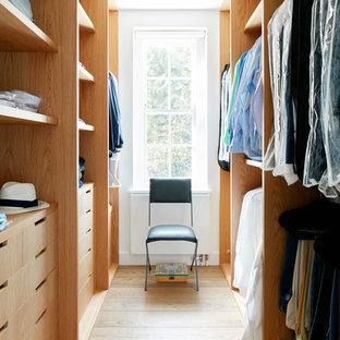 Foto de armario vestidor unisex, actual, de tamaño medio, con armarios abiertos, puertas de armario de madera clara y suelo de madera clara