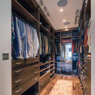 ロンドンの男女兼用トランジショナルスタイルのおしゃれなウォークインクローゼット (オープンシェルフ、濃色木目調キャビネット、濃色無垢フローリング、茶色い床) の写真
