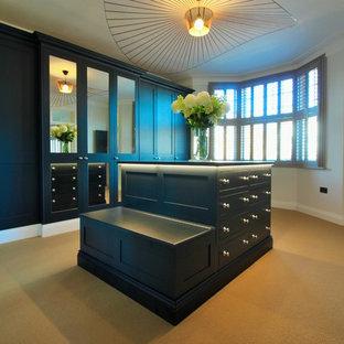 Immagine di un'ampia cabina armadio unisex minimal con ante in stile shaker, ante blu, moquette e pavimento beige