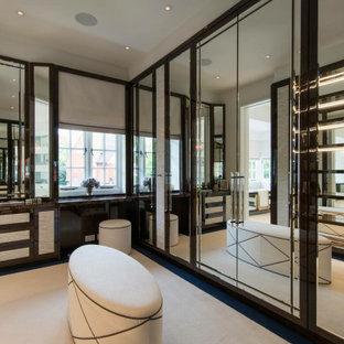 Ejemplo de armario vestidor unisex, minimalista, grande, con armarios tipo vitrina, puertas de armario marrones, moqueta y suelo beige