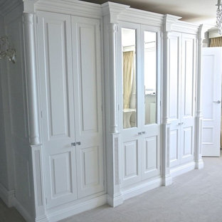 Design ideas for a traditional gender neutral wardrobe in Dorset with raised-panel cabinets, white cabinets and carpet.