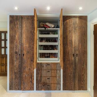 Ejemplo de armario unisex, clásico, de tamaño medio, con armarios con paneles lisos, puertas de armario de madera oscura, moqueta y suelo beige