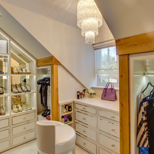 Large traditional walk-in wardrobe for women in Other with recessed-panel cabinets, beige cabinets, carpet and beige floors.