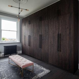 Ejemplo de armario vestidor unisex, contemporáneo, de tamaño medio, con armarios con paneles lisos, puertas de armario de madera en tonos medios, suelo de madera oscura y suelo marrón