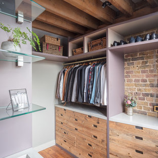 Photo of a large industrial gender-neutral walk-in wardrobe in London with flat-panel cabinets, light wood cabinets, medium hardwood floors and brown floor.